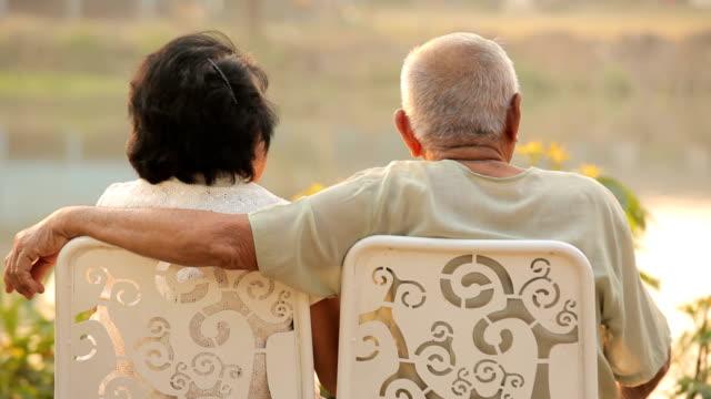 Senior couple sitting near river during sunset