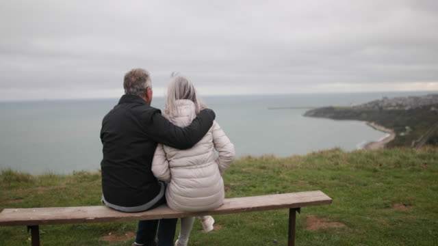 Senior couple sitting on a bench looking at sea view
