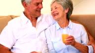 Senior couple sitting on couch having orange juice