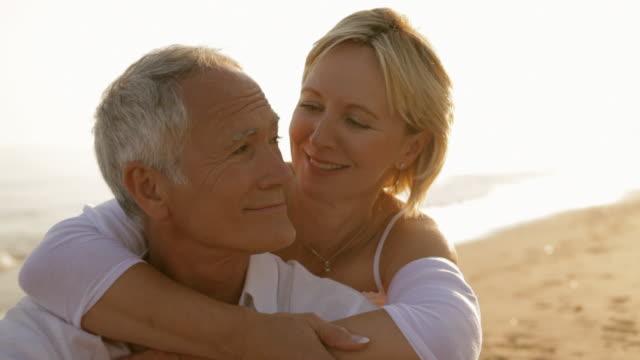 senior couple sitting together on beach