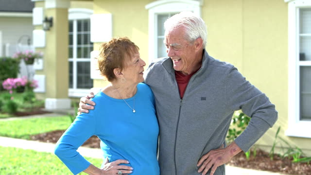 Senior couple standing together outside their home