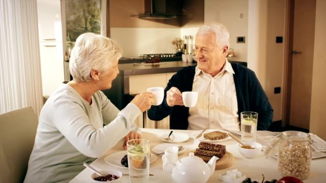 Altes Paar reden beim Frühstück