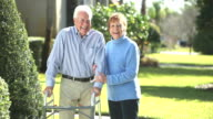 Senior couple talking outdoors, man using walker