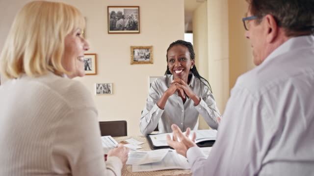 Senior couple talking to an African-American insurance agent at a meeting in their home