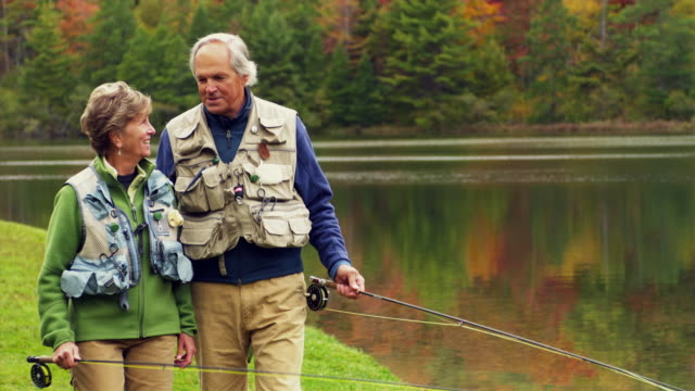 MS SHAKY PAN Senior couple talking while walking along lake shore carrying fishing rods, Manchester, Vermont, USA