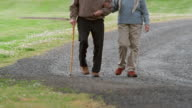 MS TU Senior couple walking arm in arm along dirt road / Washington State, USA