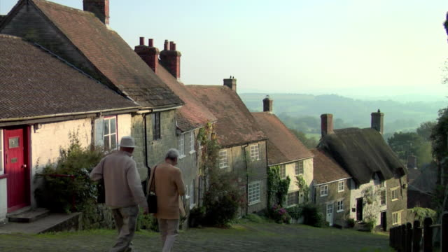 WS Senior couple walking down Gold Hill past cottages / Shaftesbury, England