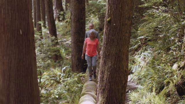 Senior couple walking on a log through the woods
