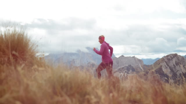 SLO MO DS Senior female runner running a marathon across a mountain meadow