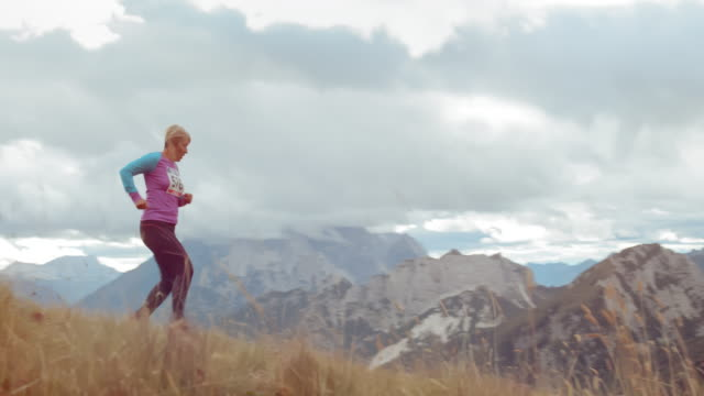 DS Senior female runner running a marathon in the mountains on a grassy trail