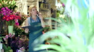 MS Senior Florist speaks on the phone whilst inspecting supplies in her shop