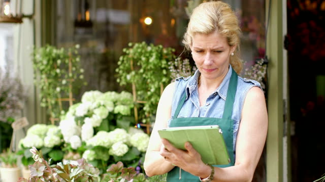 MS A Senior Florist stands at the entrance of her shop, inspecting her flowers and typing into her digital tablet