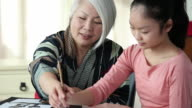 MS Senior Grandmother Teaching Granddaughter Traditional Asian Calligraphy Painting / Richmond, Virginia, United States