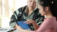 MS Senior Grandmother Teaching Granddaughter Traditional Asian Calligraphy Painting on Tablet Computer / Richmond, Virginia, United States