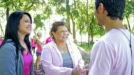 Senior Hispanic woman signing up for breast cancer awareness race with granddaughter