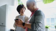 Senior Japanese Man Showing Smart Phone to Wife