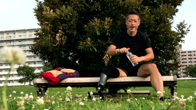 Senior Japanese man with a prosthetic leg resting after his fitness routine