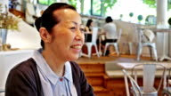 Senior Japanese Woman Smiling in a Cafe