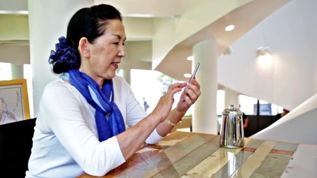 Senior Japanese Woman Using A Smart Phone