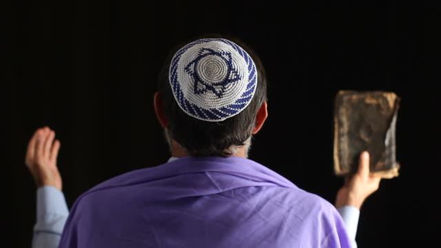 Senior jewish man praying ,holy book in hand