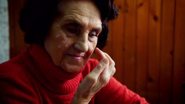 Senior lady applying face cream