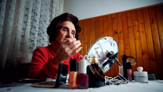 Senior lady applying lipstick
