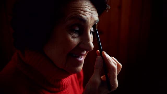 Senior lady applying make up