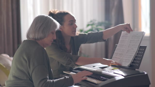 Senior lady learning synthesizer with young female volunteer
