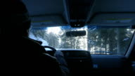 Senior male driving car down snow white road