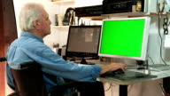 senior male in wheelchair working at a computer