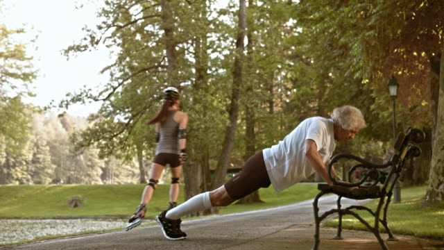 DS Senior male runner doing push ups on a park bench