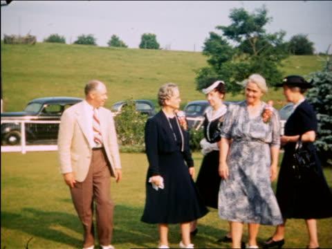 1940 senior man + 4 senior women in formalwear standing in grass outdoors / Maplewood, NJ