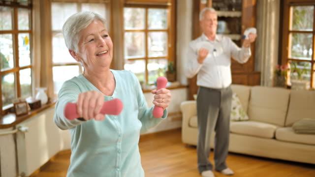 SLO MO senior man en vrouw doen gewicht oefeningen