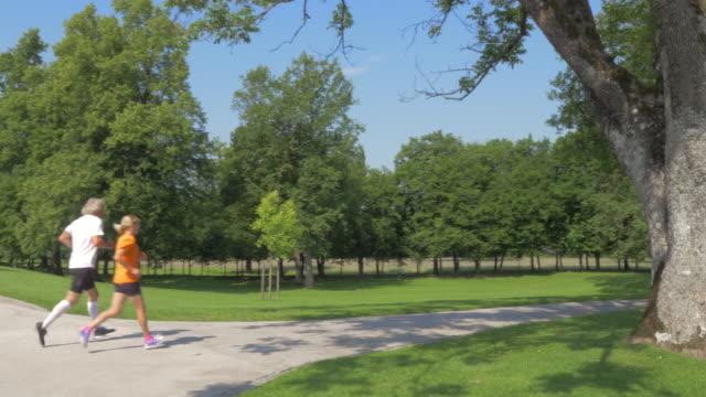 AERIAL Senior man and woman jogging through a park