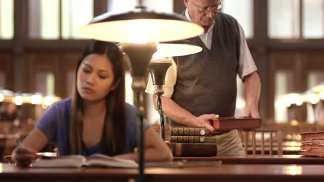DS alter Mann mit einem Buch auf Schreibtisch in Bibliothek