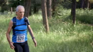 SLO MO DS Senior man competing in a trail marathon in the forest