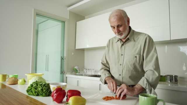 Senior man cooking a healthy meal at home