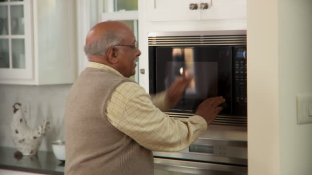 MS, PAN, Senior man cooking meal in microwave and chopping tomatoes, Richmond, Virginia, USA