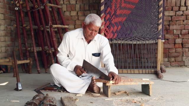 Senior man cutting wood with a saw, Haryana, India