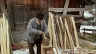 MS ZO Senior man cutting wood with hatchet / Gimmelwald, Berner Oberland, Switzerland