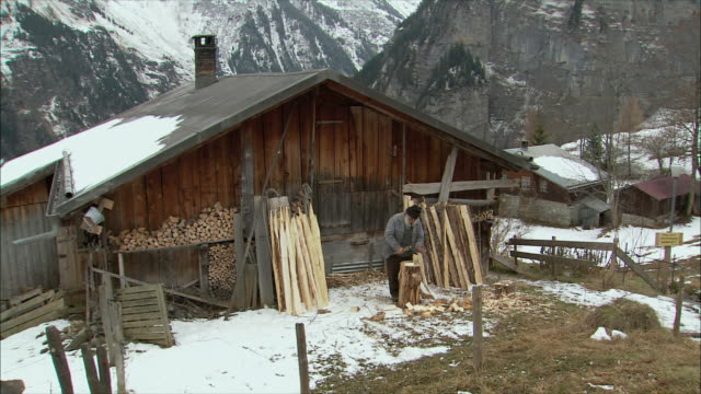 WS Senior man cutting wood with hatchet / Gimmelwald, Berner Oberland, Switzerland