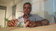 Senior man depositing money at bank counter, Delhi, India