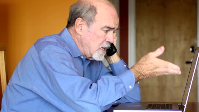 Senior Man Discusses Documents over Phone
