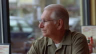 CU, Senior man drinking coffee in diner