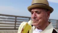 MS Senior man eating banana / Jacksonville Beach, Florida, USA