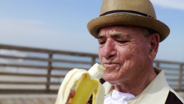 MS Senior man eating banana / Jacksonville Beach, Florida, USA