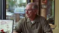 CU, Senior man eating hamburger in diner