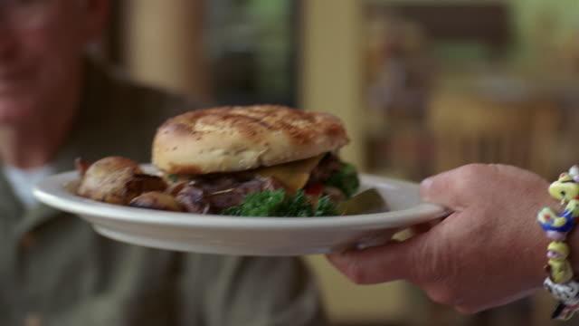 CU, TU, Senior man eating hamburger in diner