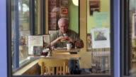 MS, Senior man eating hamburger in diner