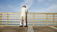 WS Senior man fishing off pier / Jacksonville Beach, Florida, USA